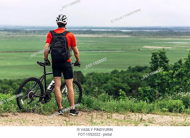 Rear view of man with mountain bike standing on hill