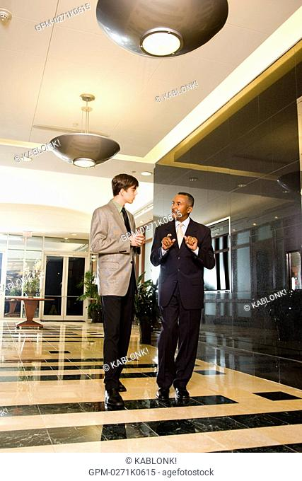 Businessmen walking through lobby of office building while talking