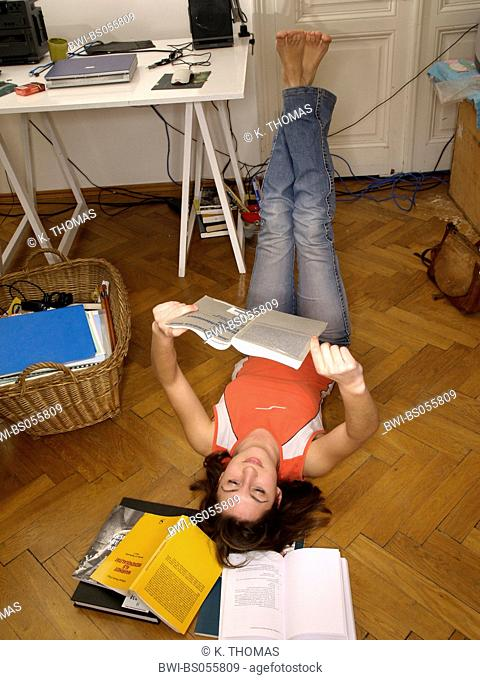Young Woman / twen, lying on the floor in the midst of books reading legs up