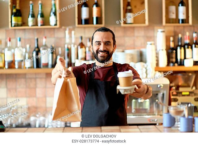 small business, people, takeaway and service concept - happy man or waiter in apron holding coffee cups and paper bag at bar