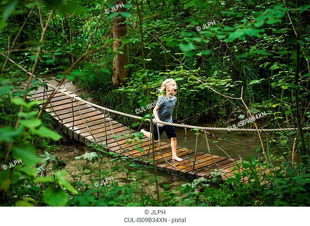 Boy running across pedestrian rope bridge in forest