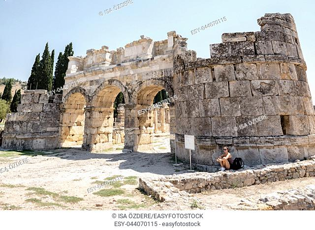 Woman sits near Byzantine Gate at Hierapolis ancient city in Pamukkale, Turkey. 25 August 2017