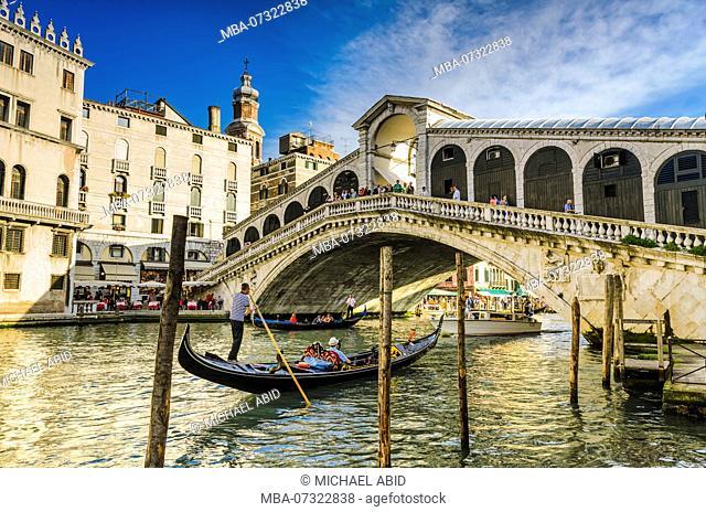 Gondola at the Rialto bridge with evening light in Venice, Italy