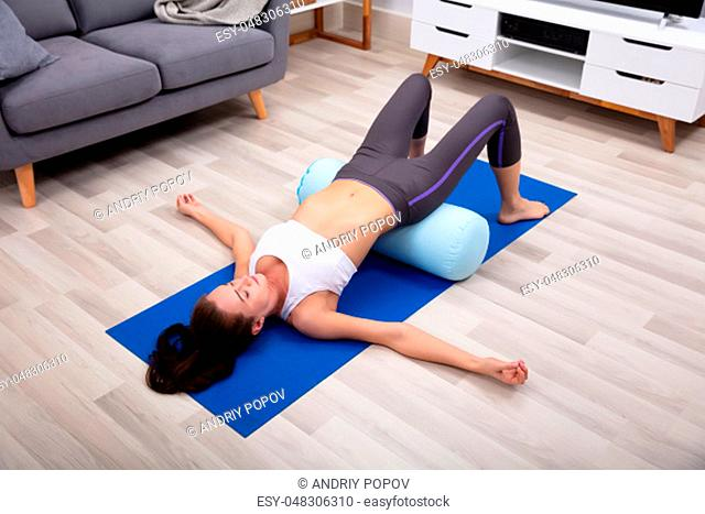Young Woman Practicing Yoga On Bolster At Home