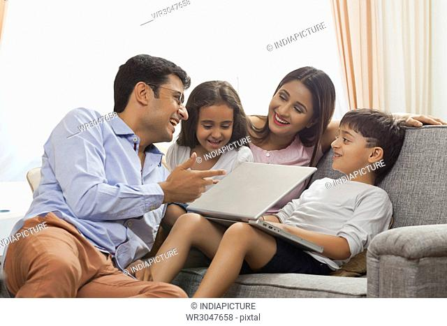 Boy using laptop with his family smiling and enjoying spending time together