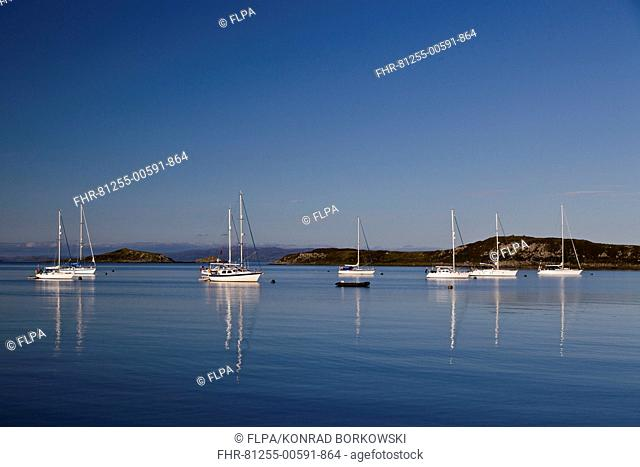 View of yachts moored in bay, with Small Isles in background, Craighouse Bay, Isle of Jura, Inner Hebrides, Scotland