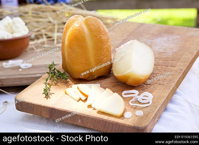 Smoked cheese slices and big piece on wooden board