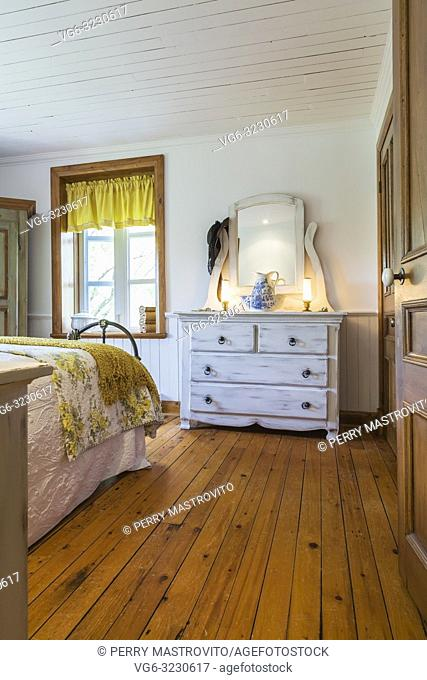 Partial view of king size bed with white and yellow flowery bedspread and cream coloured antique finish wooden dresser in master bedroom inside an old 1892...