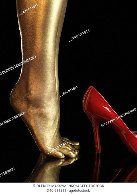 Woman bare legs covered with gold and red high heel shoes  Isolated on black background