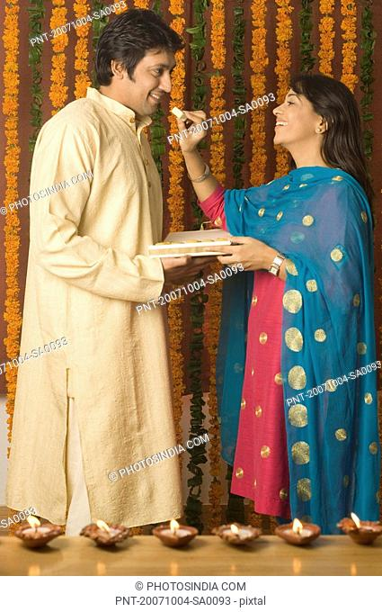 Side profile of a young woman feeding a piece of burfi to a mid adult woman and smiling