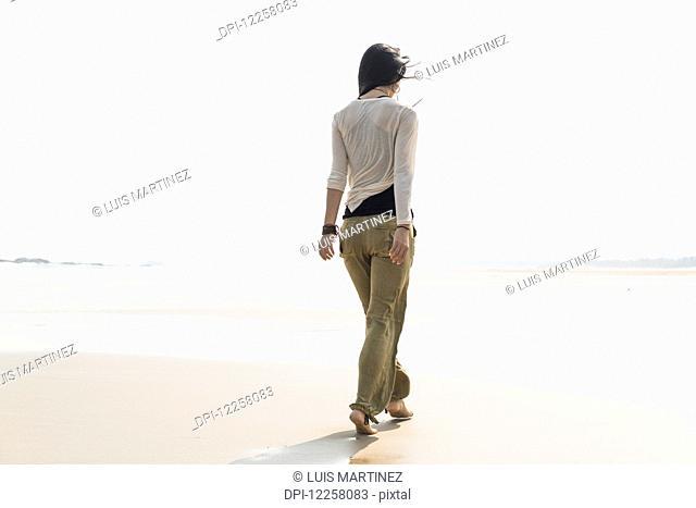 Young woman walking on the beach; Huohu, Taiwan