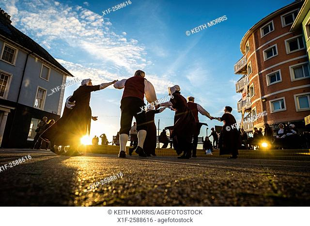 A group of people in traditional costume folk dancing on Aberystwyth promenade at sunset, August evening, summer 2015