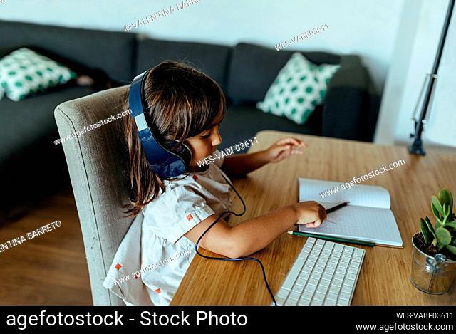 Female preschooler wearing headphones at desk