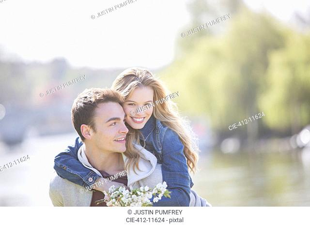 Man carrying girlfriend outdoors