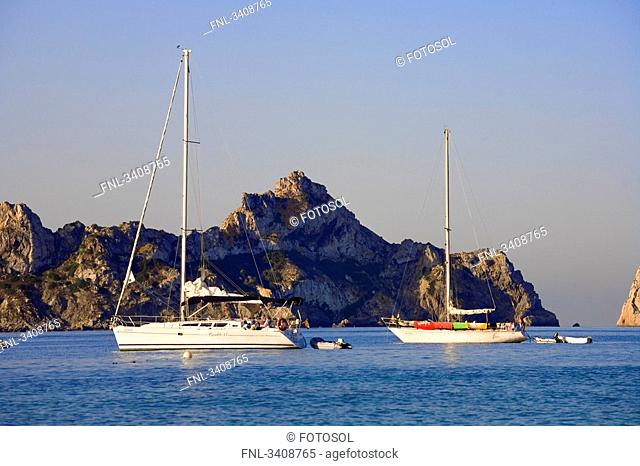 Sailing yachts in front of a rocky island Es Vedra, Ibiza, Spain