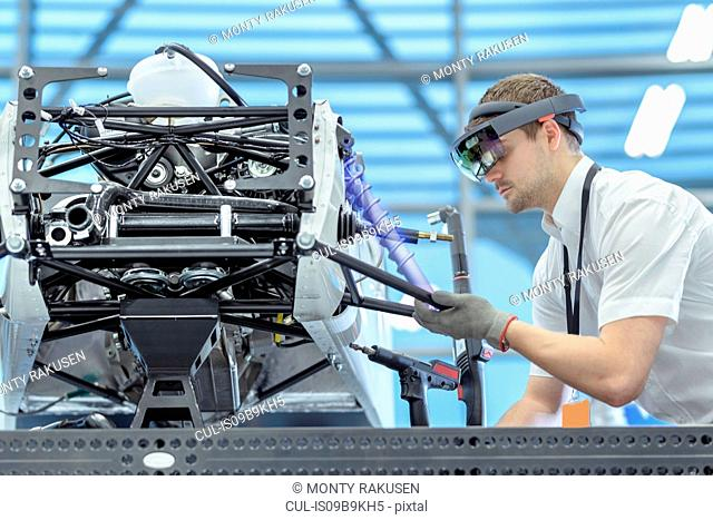 Engineer using augmented reality headset to 'see' parts position on car in assembly composite image showing CAD drawing of part in robotics research facility