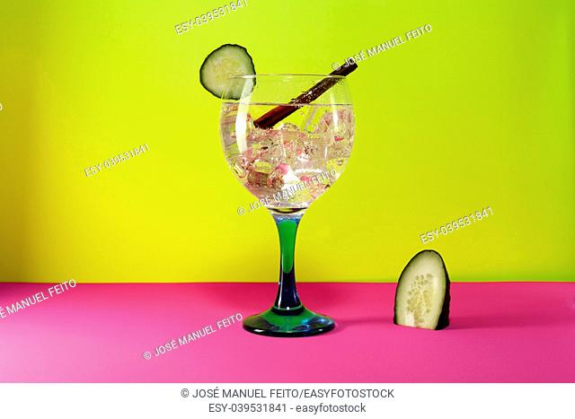 gin tonic with lemon slice, cinnamon stick and lemon segment on pink and yellow background