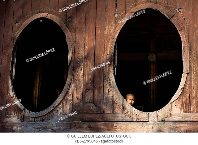 A young novice Buddhist monk sitting by the oval windows of the Shwe Yan Pyay Monastery in Nyaungshwe, Myanmar