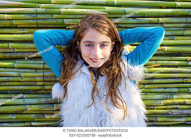 Kid girl relaxed in green canes background in autumn winter