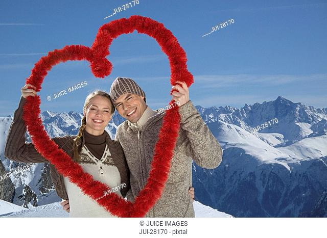 Young couple in mountains on winter day holding red heart