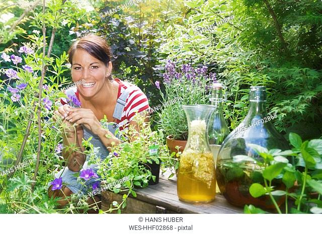 Austria, Salzburger Land, Young woman in garden, squatting among flowers