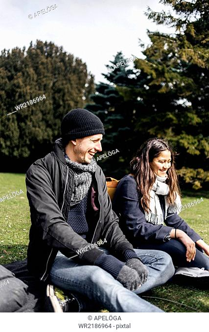Happy young couple sitting at park