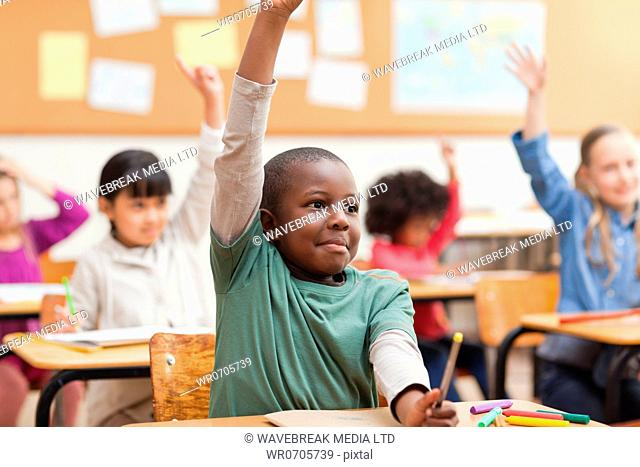 Young pupils raising their hands during class