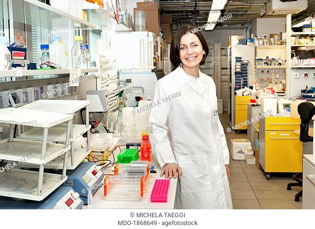 Researcher in white coat, smiling next to the laboratory bench. Trento (Italy), February 2014