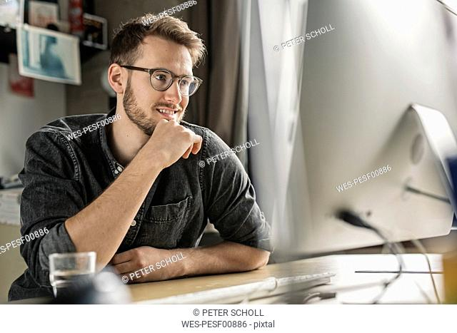Smiling young man working on computer at desk at home