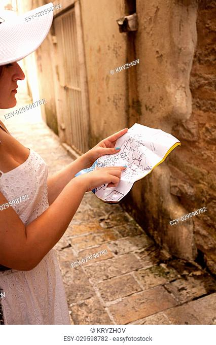 Closeup photo of woman lost in old city pointing at map