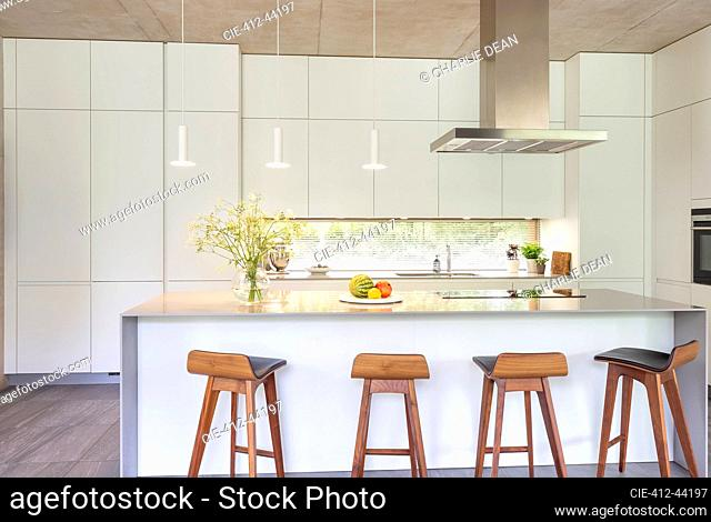 Modern white kitchen with island and barstools