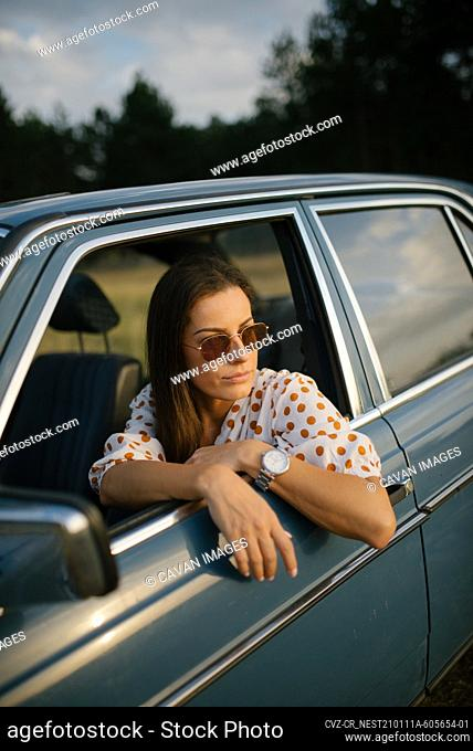 A young woman looking out of the open car window