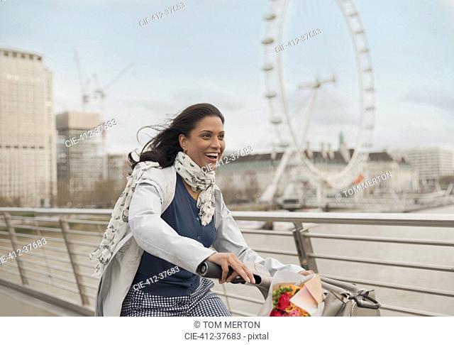 Enthusiastic, smiling woman bike riding on bridge near Millennium Wheel, London, UK