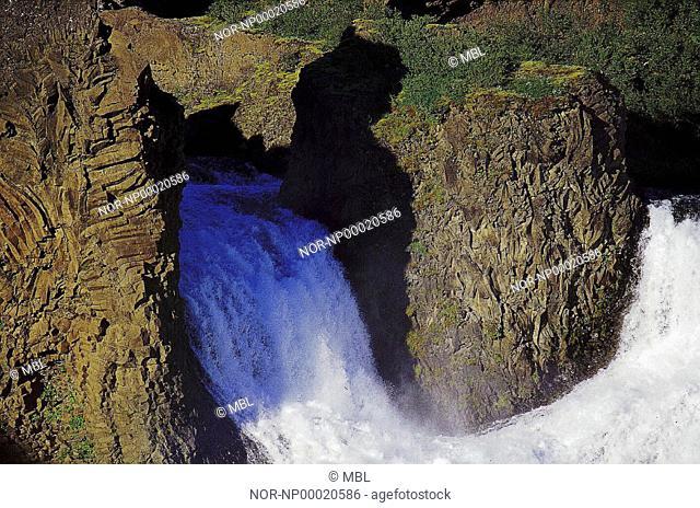 A waterfall, cliffs around it