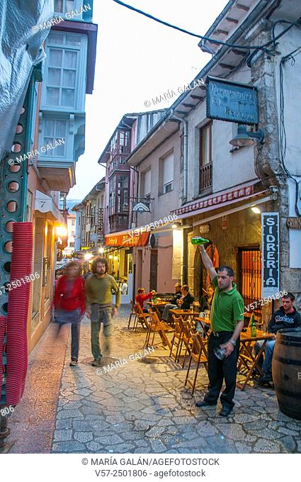 Waiter serving cider in the street. Llanes, Asturias, Spain