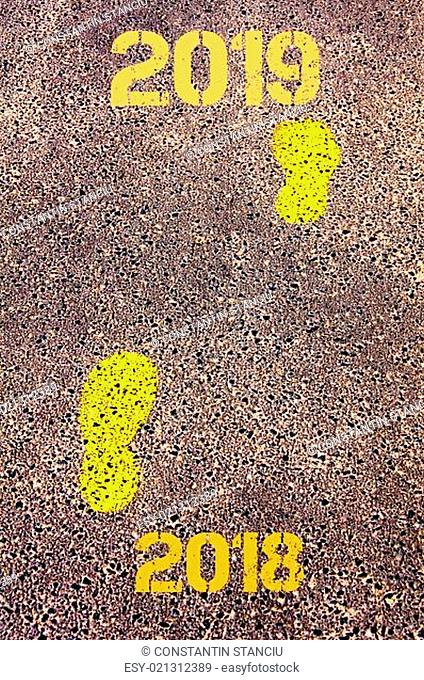 Yellow footsteps on sidewalk from Year 2018 to Year 2019 messages.New Years Concept image