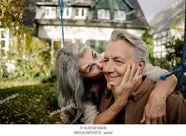 Happy woman hugging an kissing senior man on a swing in garden
