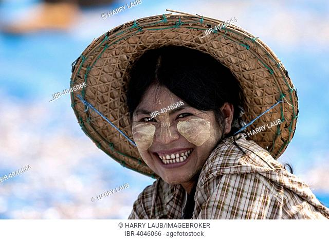 Local woman with a straw hat and Thanaka paste in her face, portrait, Ngapali, Myanmar