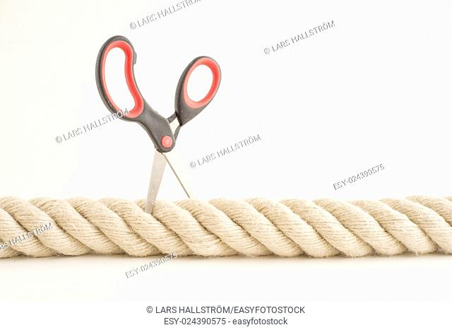 Strong rope and small scissors. Concept of strength, challenge and difficulty