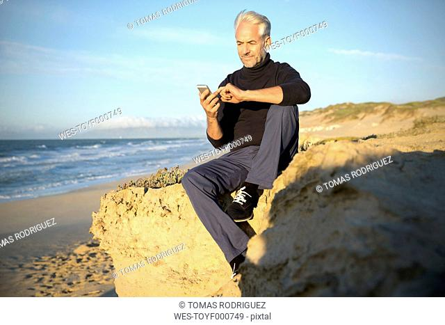 South Africa, portrait of man sitting on a rock at the beach using smartphone