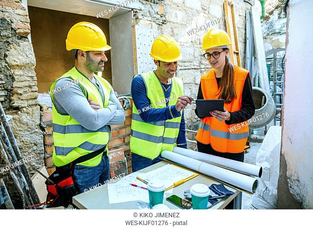 Woman and two construction workers with tablet on construction site