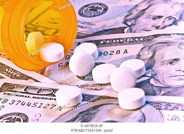 Pills spilling out on paper currency