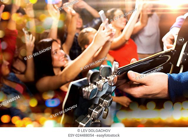 holidays, music, nightlife and people concept - close up of musiciab playing electric guitar on stage over happy people crowd taking picture by smartphones and...