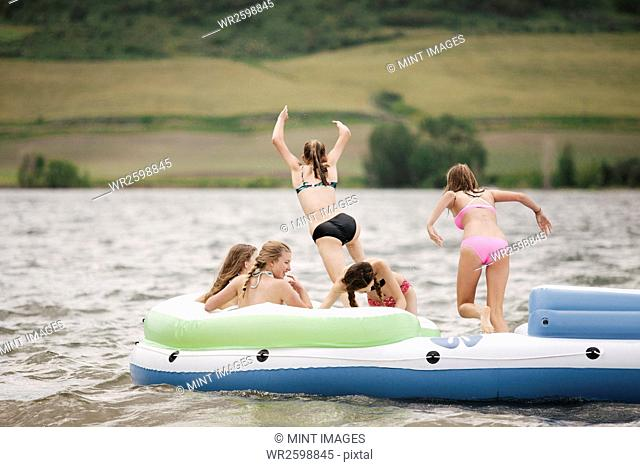 Teenage girls in an inflatable dinghy on a lake