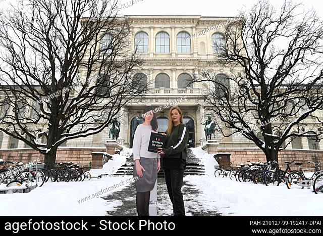 27 January 2021, Bavaria, Munich: Artist Janine Mackenroth (r) stands in front of the Munich Art Academy with a cardboard cutout of Bianca Kennedy and the joint...