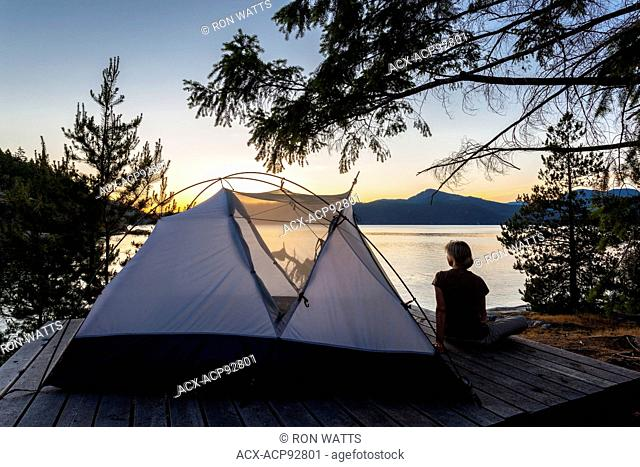A camper relaxes on a platform next to her tent at dusk. West Curme Island, Desolation Sound Marine Park, British Columbia, Canada. Model Released