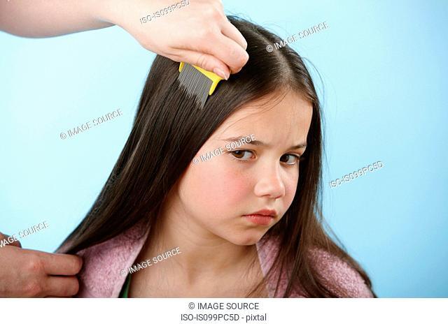 Parent combing daughter's hair with headlice comb