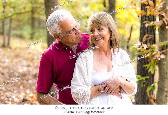 A mature couple outdoors, hugging, talking and laughing, looking at each other