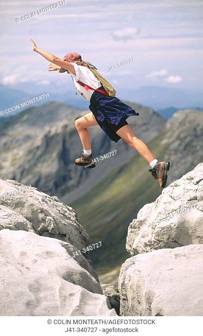 Female hiker leaping across rocks. New Zealand