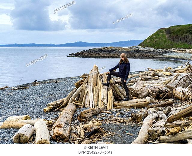 A young woman stands on driftwood on Spiral Beach, Vancouver Island; Victoria, British Columbia, Canada